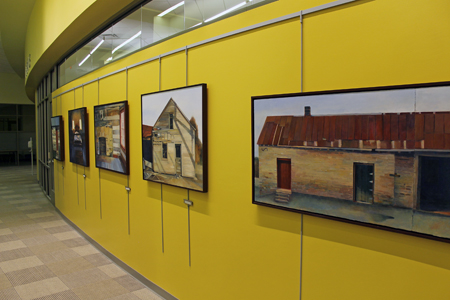 "In addition to the ""Riparian Zone"" art wall created by Joan Gardiner, the library also features a wall of paintings depicting local history."